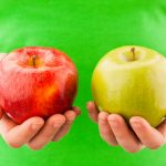 Woman comparing green and red apple
