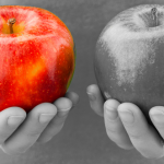 Hands comparing two types of apples